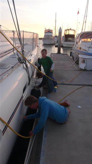 Washing the paint that scraped onto our boat.